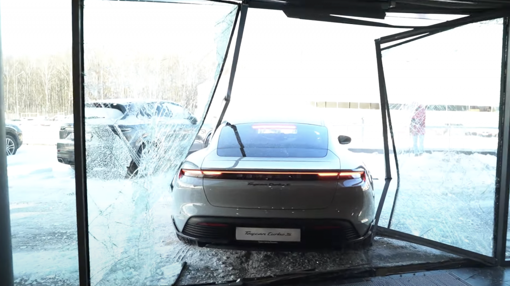 An image of a 2021 Porsche Taycan Turbo S slamming through the windows of a dealership.