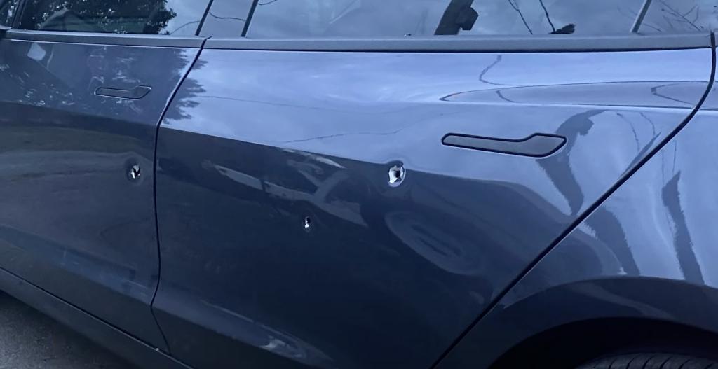 An image of a Tesla Model 3's door showing bullet holes.