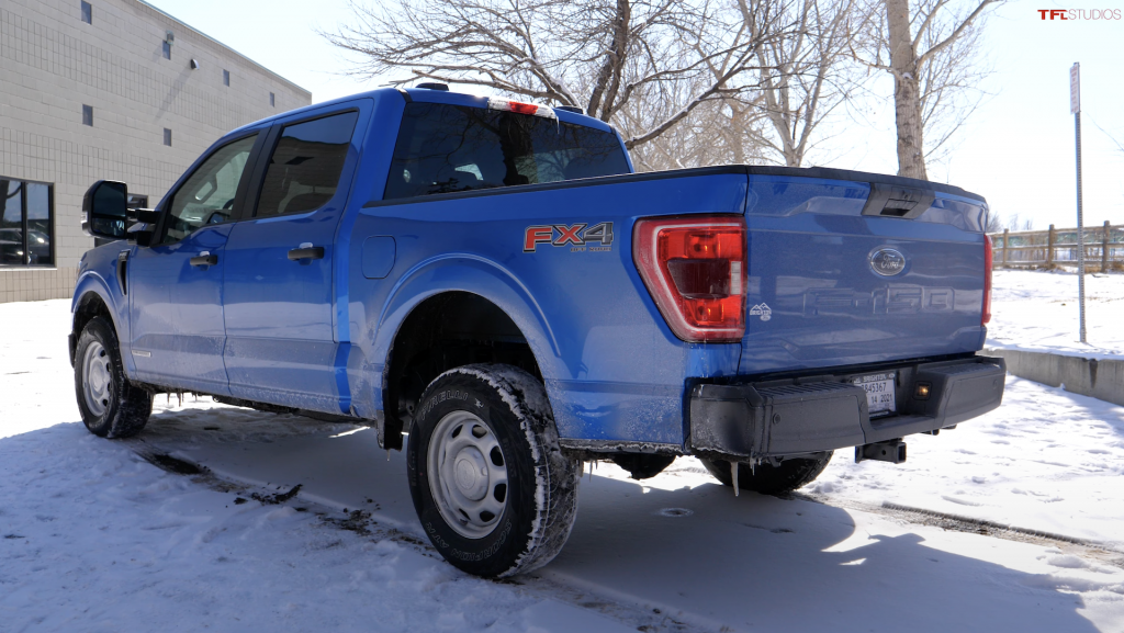 An image of a blue Ford F-150 parked outside on the snow.