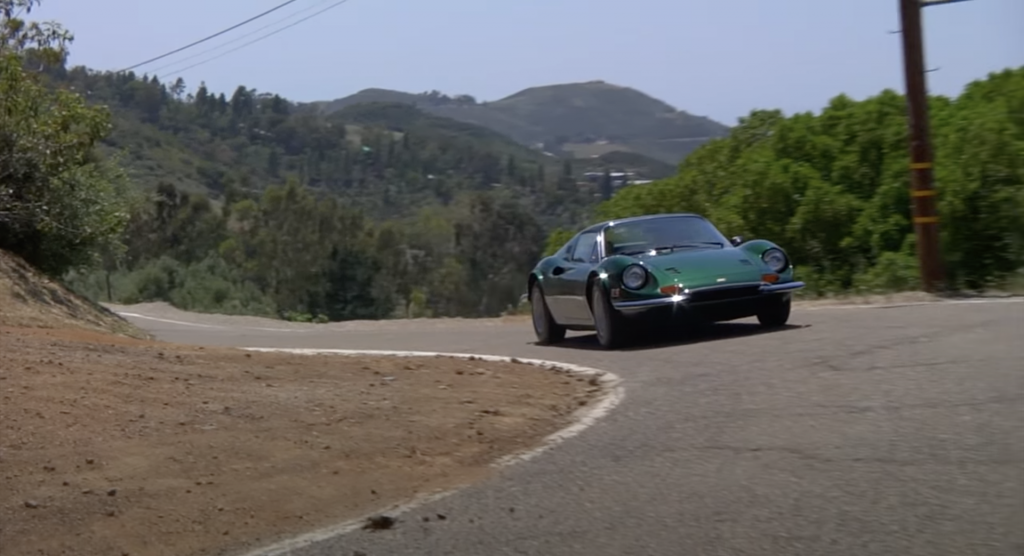 An image of a Ferrari Dino rolling down the road.