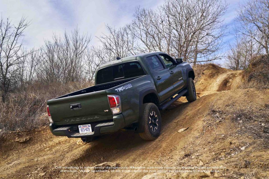 An image of a 2021 Toyota Tacoma with upgraded TRD lift kit ground clearance outside off-roading.