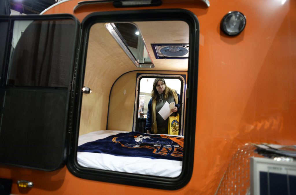 A woman takes a look inside of a teardrop camper at an RV show