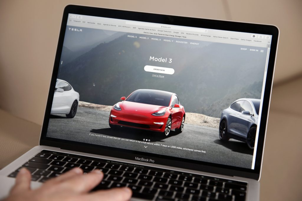 A person browsing Tesla Model 3 cars on the company's website