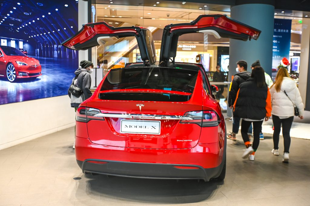 Customers watch a Model X vehicle at a Tesla flagship store