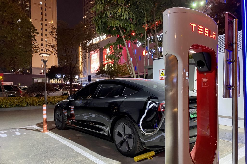 An electric vehicle charges at a Tesla charging station on February 2, 2021