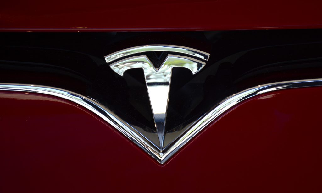 The Tesla logo on the nose of a red electric sedan