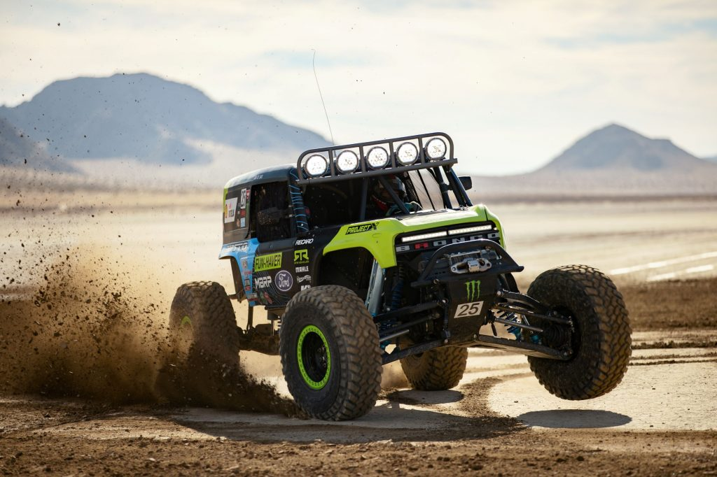 The black-and-green No. 25 2021 Ford Bronco 4400 racer slides through sand