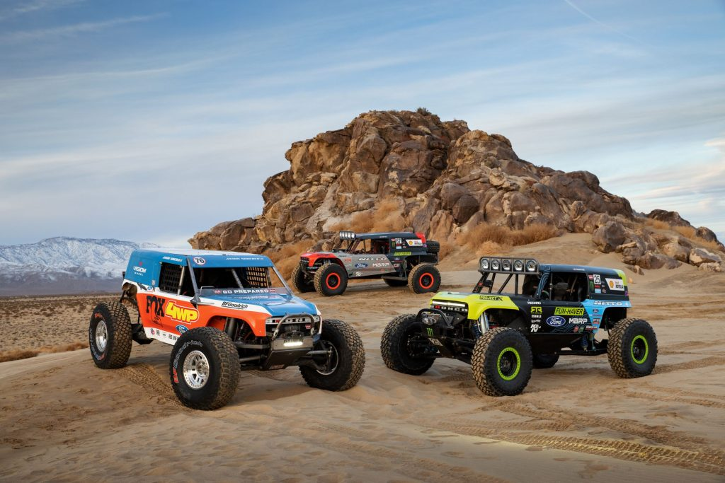 The three 2021 Ford Bronco 4400 King of the Hammers racers gathered around a desert rock formation