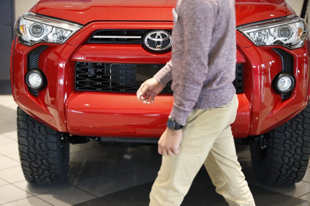 A person walks by a red Toyota 4Runner in a dealership