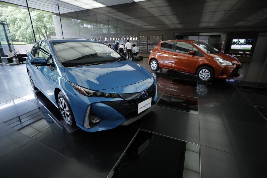 A blue Toyota Prius Prime and another red Toyota on display in a showroom
