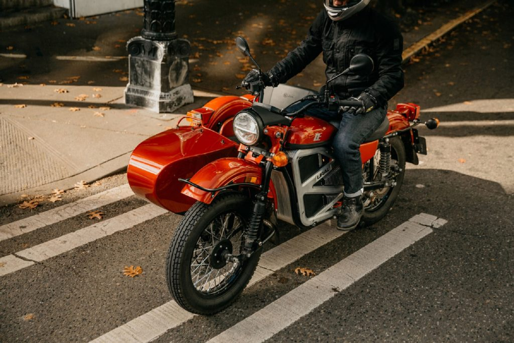 A rider on the orange Ural electric cT motorcycle concept with its sidecar on a city street