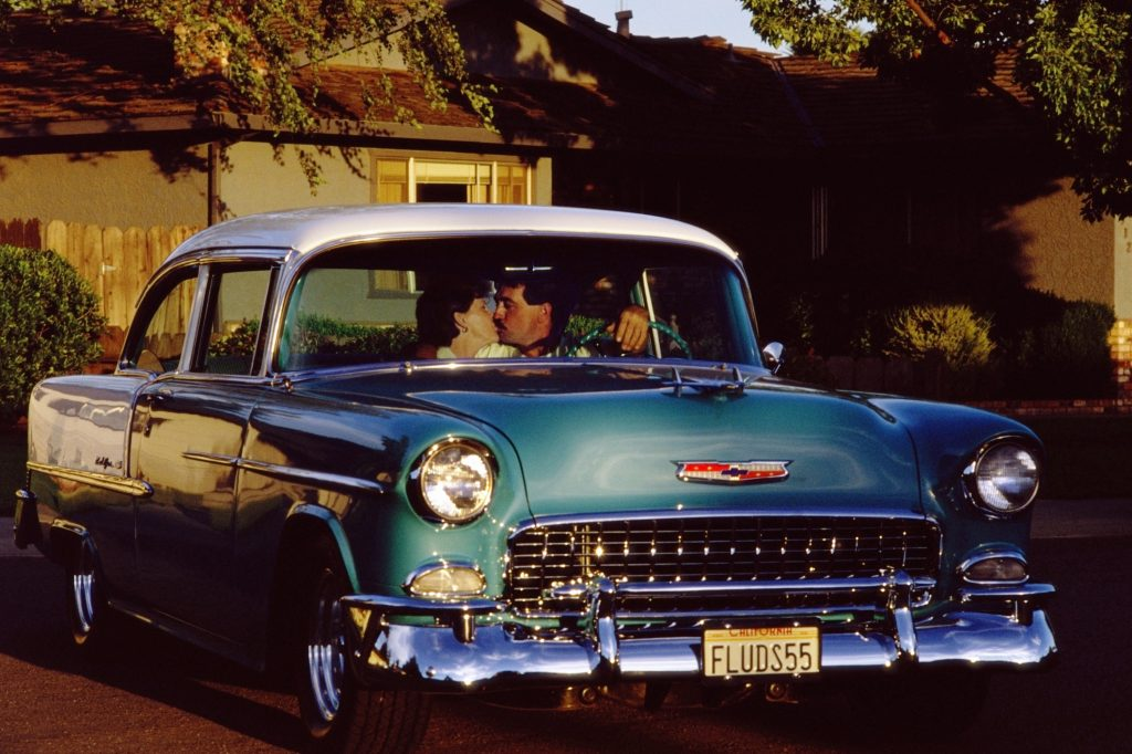 A couple kissing during a car date in a blue vintage car