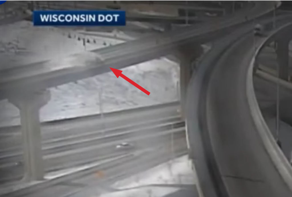 grainy image of pickup truck plunging off of overpass