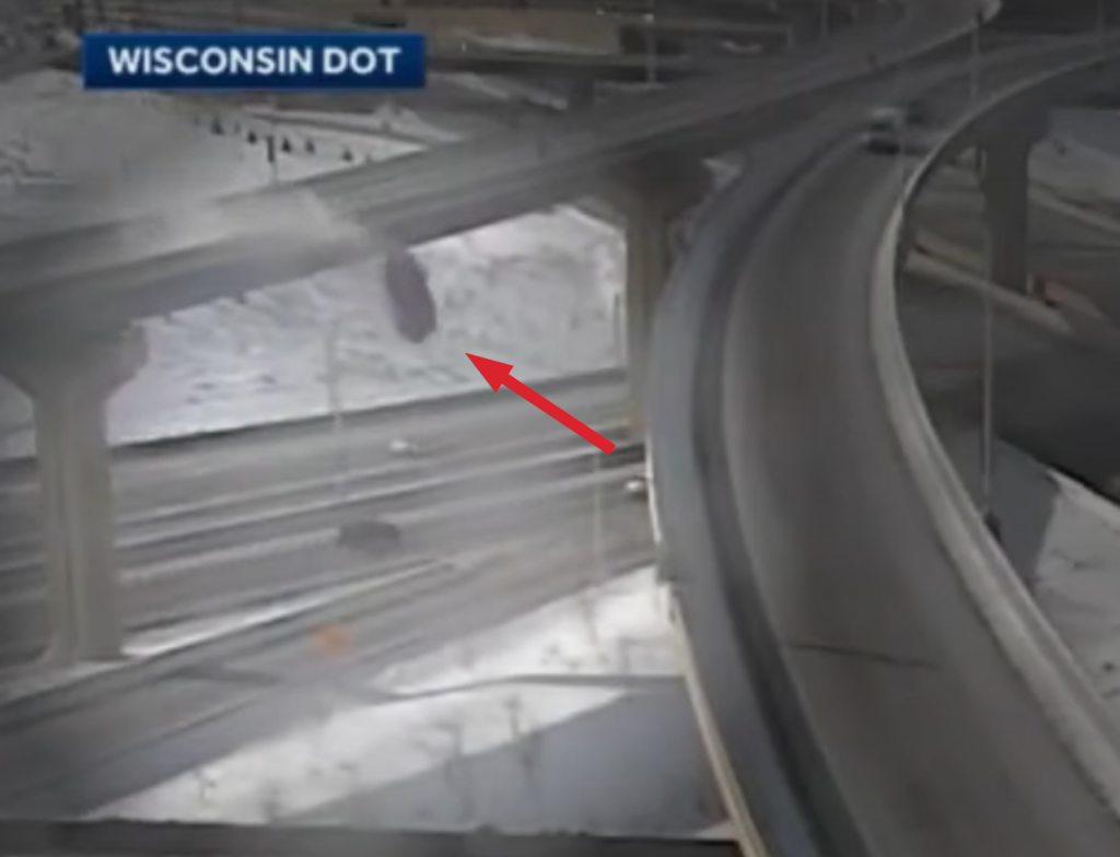 grainy image of truck plunging off of overpass