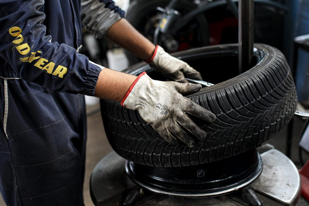 A mechanic working on a car tire.