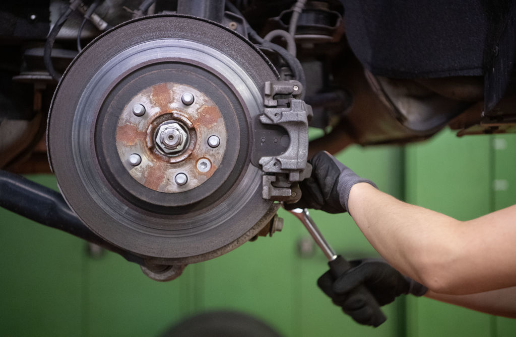 A car mechanic works on the brake disc of a car