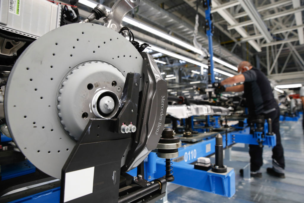 A Mercedes-Brenz brake disc on the chassis of a Mercedes S-Class as it moves across a production line