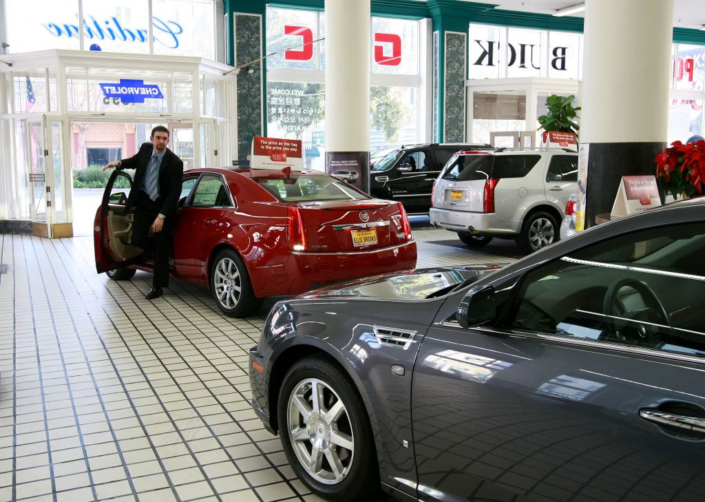 car dealership employee getting out of a car
