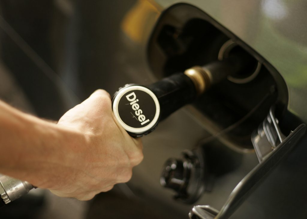 A driver fills up the tank of his car with diesel at a fuel station.
