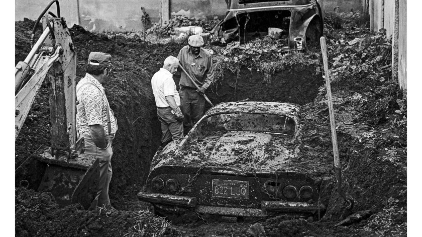 An image of a Ferrari Dino getting dug out of a hole in LA.