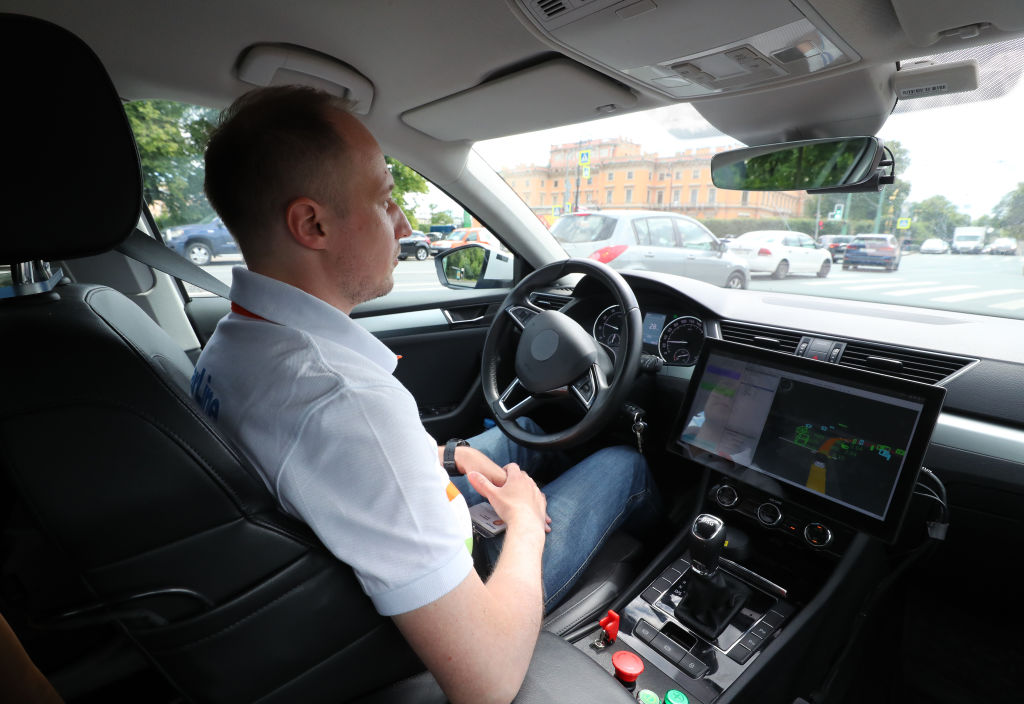 A man sits behind the wheel of a StarLine automated car as it undergoes street testing