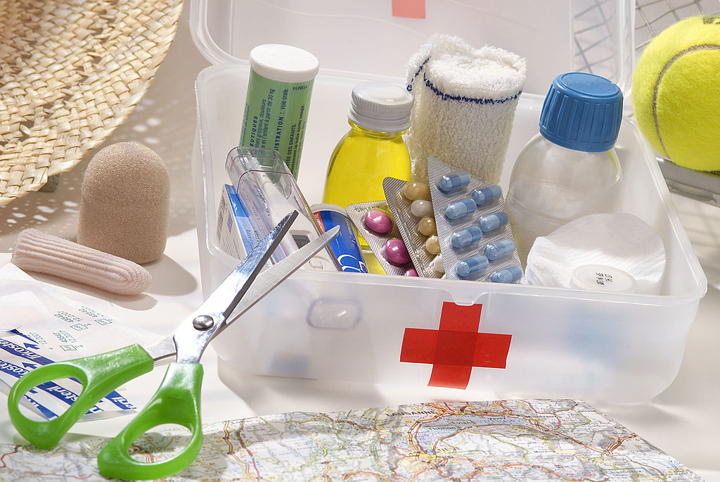 A basic first aid kit featuring bandaids, scissors, and basic medicine.