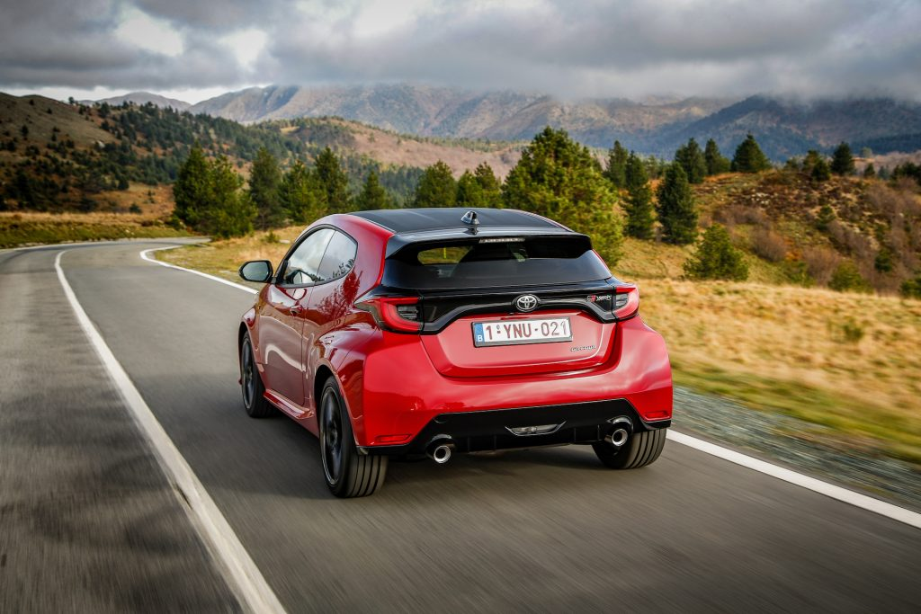 The rear 3/4 view of a red 2021 Toyota GR Yaris driving down the road