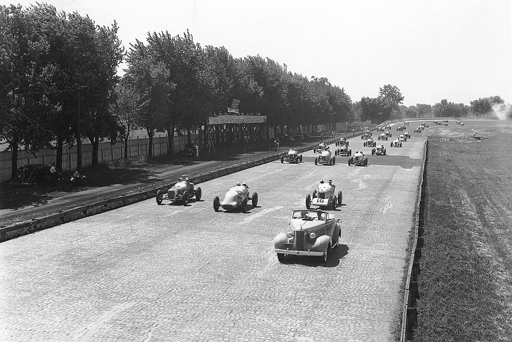 Indy cars are shown on the brick racing surface as drivers make their way around the pace lap of the Indianapolis 500 at the Indianapolis Motor Speedway, 1937 black and white