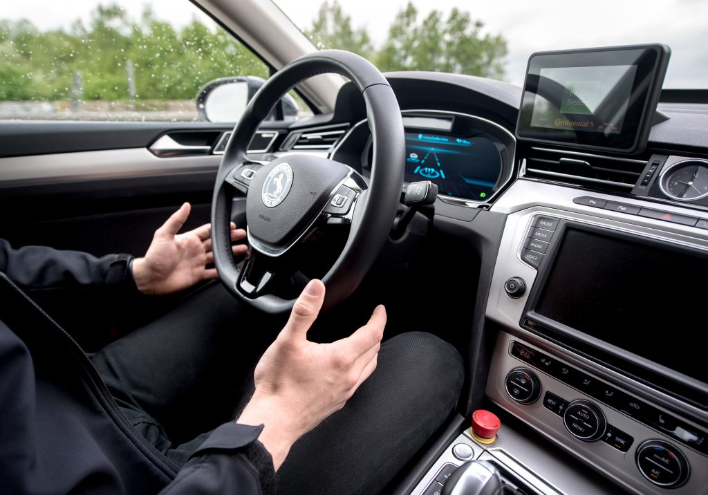 a man removes his hands from the steering wheel when driving.