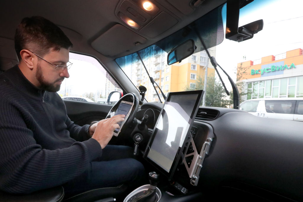 A man uses his phone as he sits in the driver's seat of a self-driving car