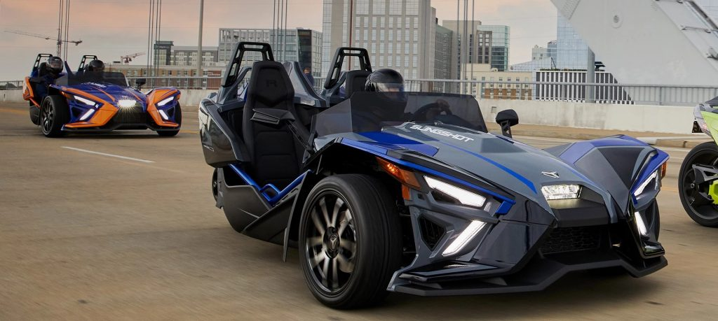 An image of a 2021 Polaris Slingshot driving down the road.