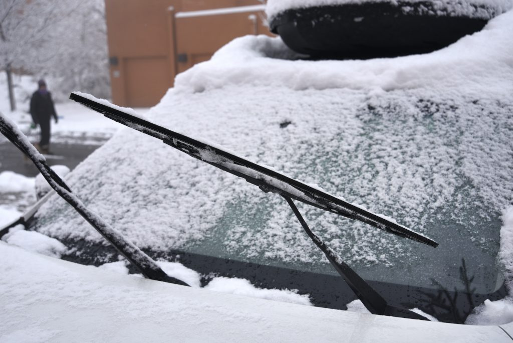 A car is covered with snow and ice after a late autumn storm in New Mexico