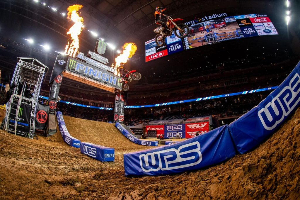 supercross riders taking a jump in a race