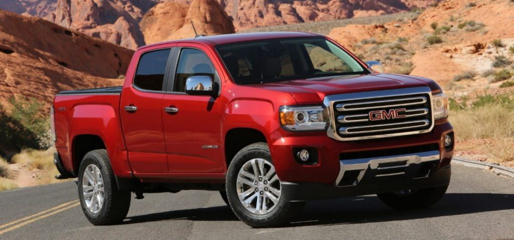 a 2018 GMC Canyon truck in red, parked on a paved mountain road