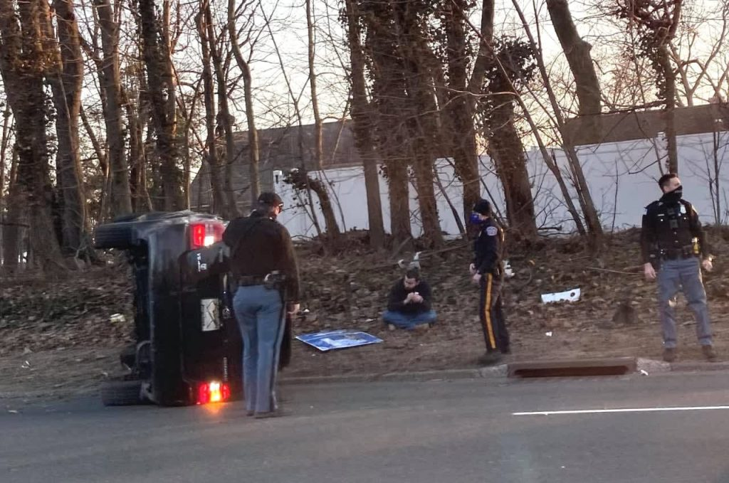 A Toyota 4Runner on its side after flipping around a curve.