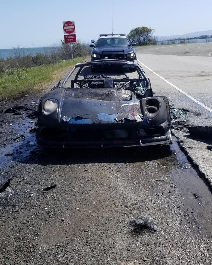 An image of a burned up Noble M400 on the side of the road.