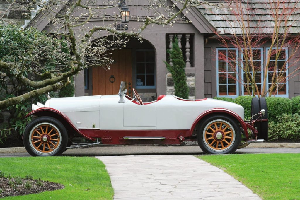 The side view of a white-and-red 1915 Crane-Simplex Model 5 46HP Boattail Tourer by an old house