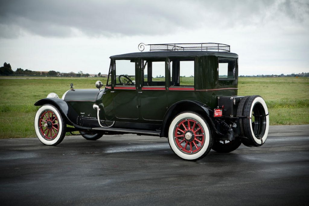 The side 3/4 view of a dark-green 1915 Crane-Simplex Model 5 Sport Berline parked on a runway