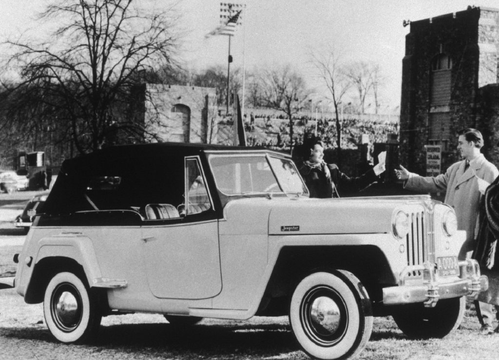 A black-and-white photo of a man and a woman with a 1948 Jeepster