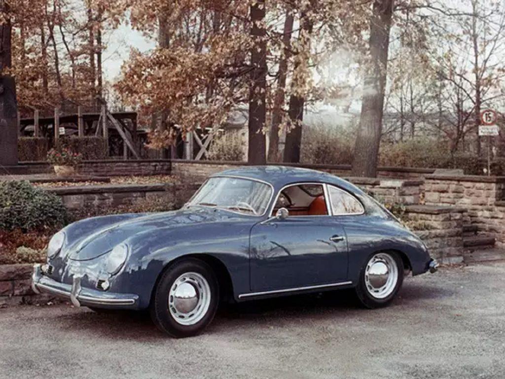 A dark-blue 1956 Porsche 356 A 1300 on a forest road