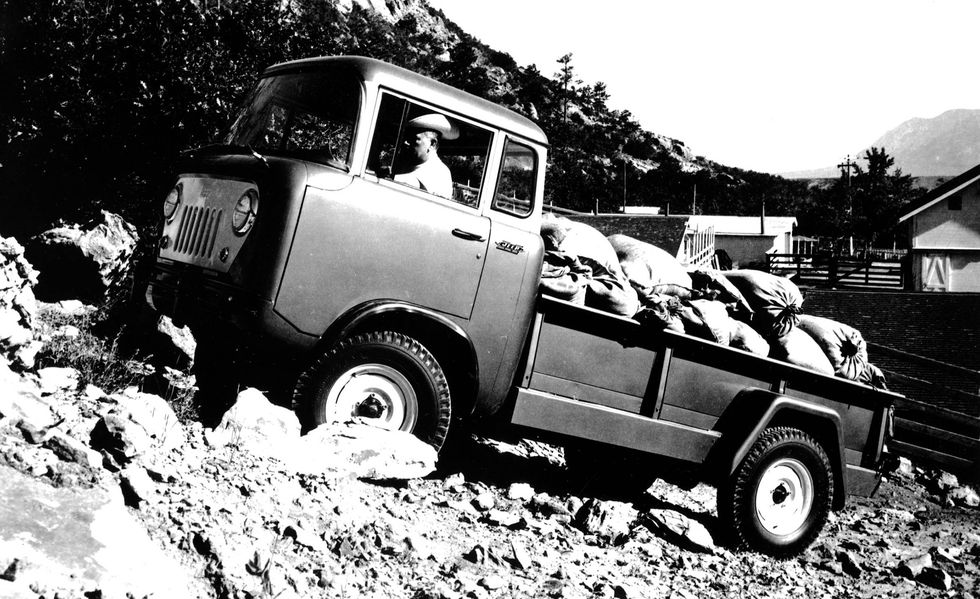 A 1957 Jeep FC crawling over the terrain