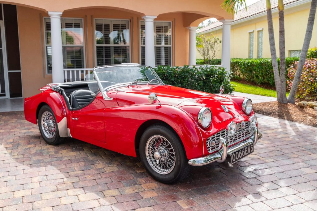 A red TR3A-spec 1960 Triumph TR3 by a peach-colored house