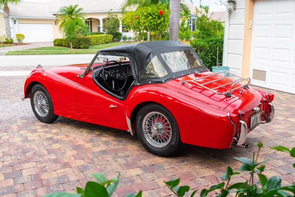 The side 3/4 view of a red TR3A-spec 1960 Triumph TR3 parked on a driveway