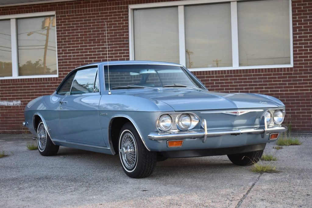 A light-blue 1965 Chevrolet Corvair Corsa by a red-brick building