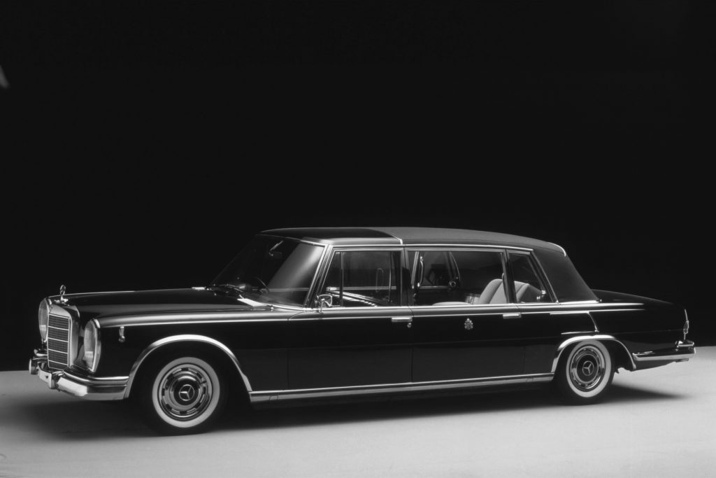A black 1965 Mercedes 600 Pullman Landaulet parked in a studio