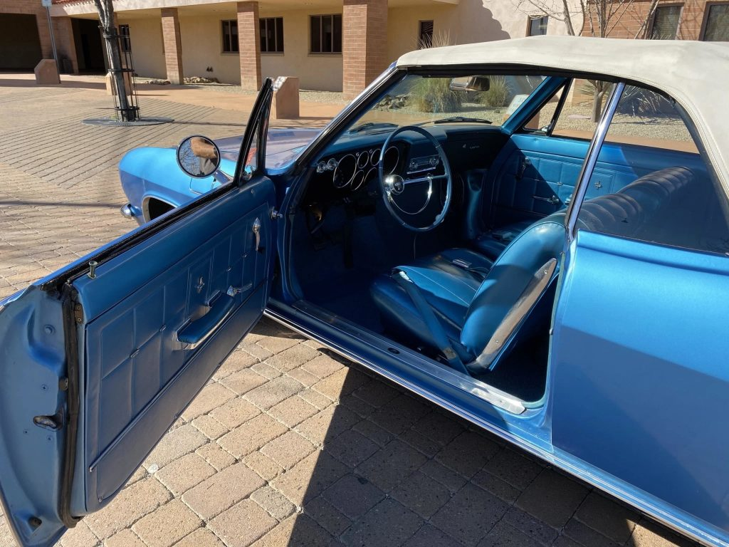 The side and blue interior of a blue 1966 Chevrolet Corvair Corsa Convertible seen from the open driver's door