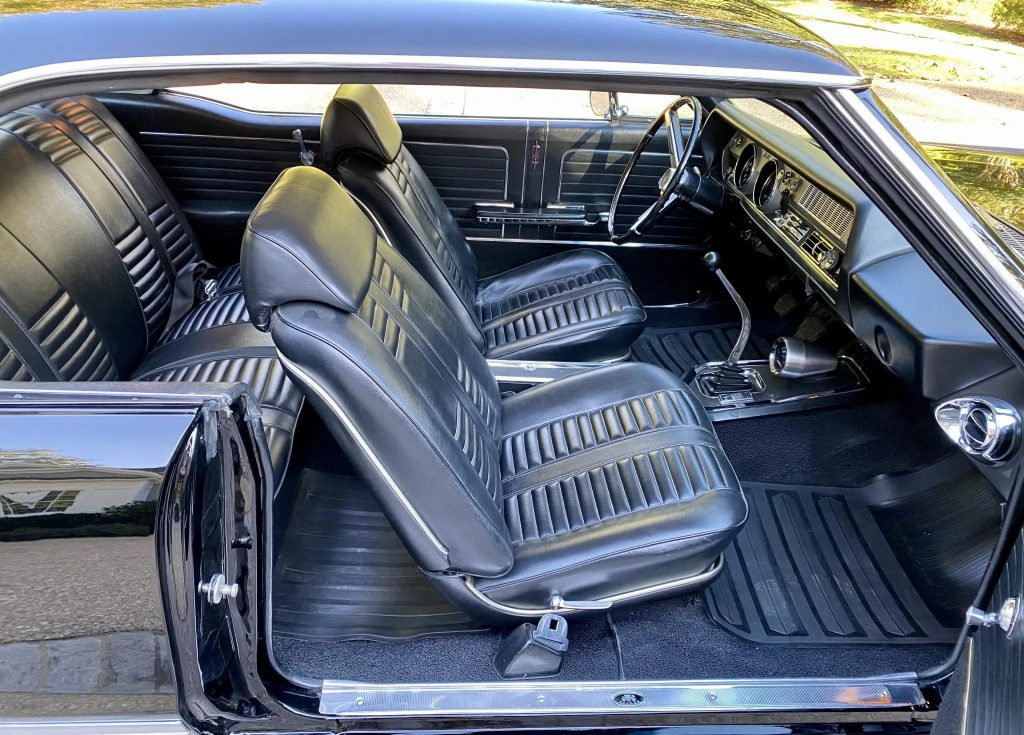 The black-vinyl interior of a black 1966 Oldsmobile 442 with a Hurst shifter