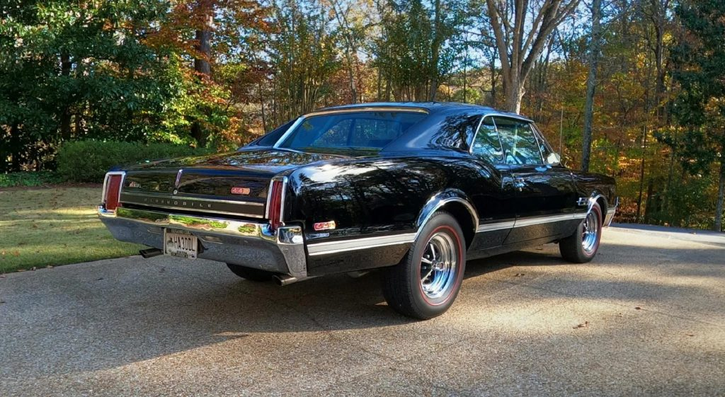 The rear 3/4 view of a black 1966 Oldsmobile 442 parked on a stone-lined driveway by some trees