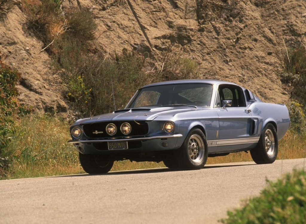 A blue-and-white 1967 Shelby GT500 Mustang driving down a canyon road