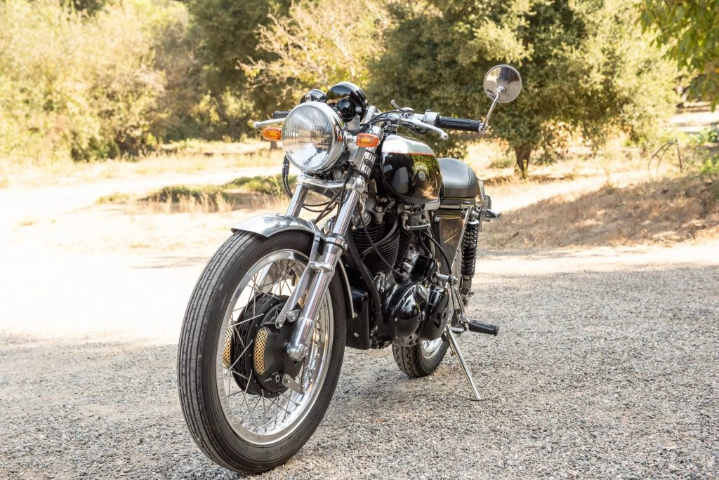 The front 3/4 view of a black-and-silver 1968 Egli-Vincent by Godet on a sunlit gravel driveway